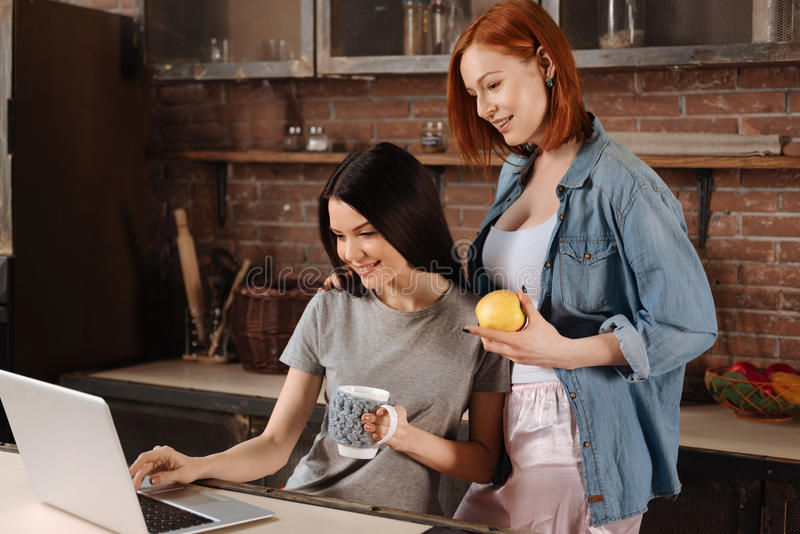 Portrait of best friends standing together. Work together. Two women spending time with pleasure while holding apple and grey cup watching film using laptop royalty free stock images