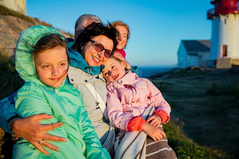 Portrait of big family, sitting on windy top of rock with lighthouse. stock photography