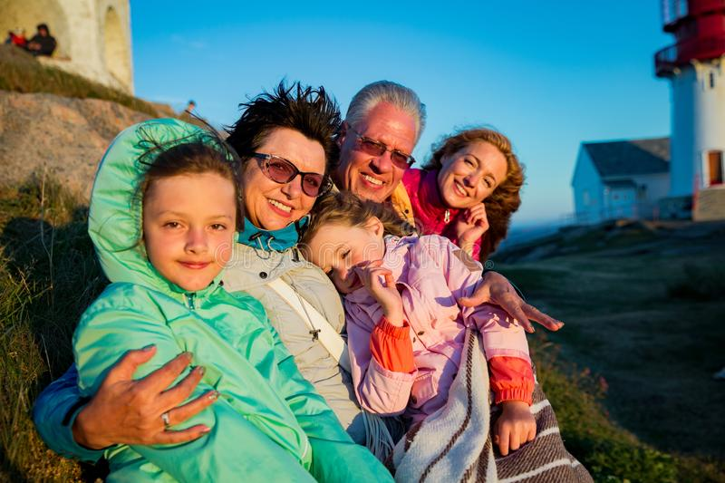 Portrait of big family, sitting on windy top of rock with lighthouse. royalty free stock photography