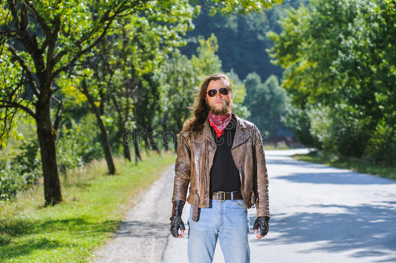 Portrait of biker man with beard standing on the road. Portrait of a young biker man with beard standing on the road. Biker is wearing leather jacket and blue royalty free stock photography