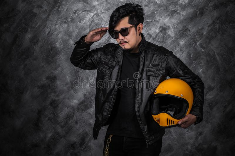 Biker man in black leather jacket saluting and holding helmet stock photos