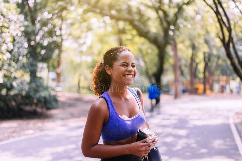 Portrait of black beautiful woman standing and resting after break workout at park,Happy and smiling,Relaxing time stock image