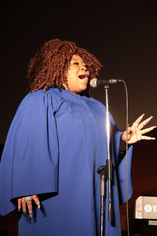 Gospel singer. Portrait of a black gospel female redhead singer, while singing and praying stock photography