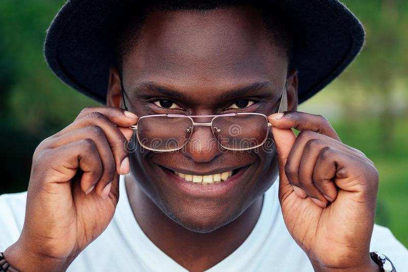 Portrait of black men in stylish suits and black hat with glasses in a summer park. African-Americans handsome model royalty free stock image
