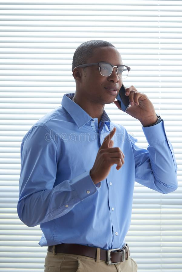 Phone call. Portrait of Black young business executive talking on the phone with coworker royalty free stock photography