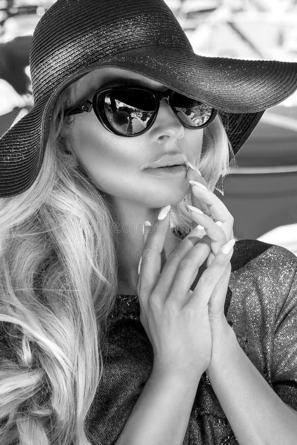 Portrait blanc du beau modèle blond sexy luxueux élégant noir utilisant un chapeau et des lunettes de soleil photographie stock libre de droits