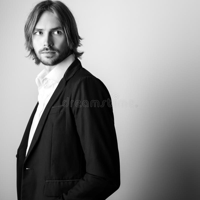 portrait blanc noir de jeune long homme beau de cheveux sur le fond de studio photo libre de droits