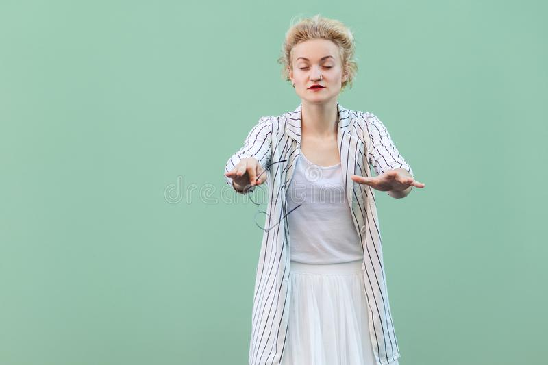 Portrait of blind young blonde woman in white shirt, skirt, and striped blouse standing, with closed eyes and trying to touch or. Find something. indoor studio royalty free stock images