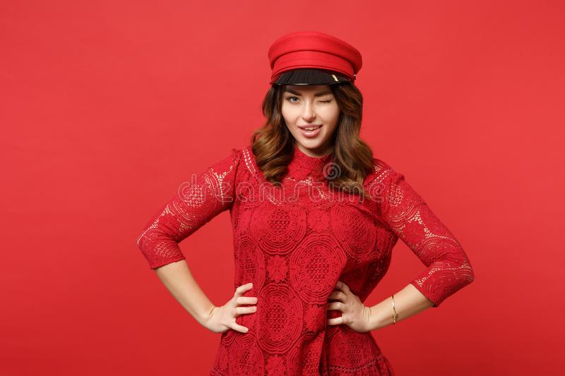 Portrait of blinking pretty young woman in lace dress, cap standing with arms akimbo isolated on bright red wall royalty free stock photography