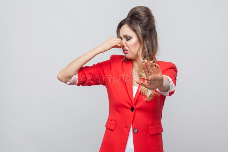 Portrait of blocking beautiful business lady with hairstyle and makeup in red fancy blazer, standing with stop gesture and closing. Her nose. indoor studio shot royalty free stock photography