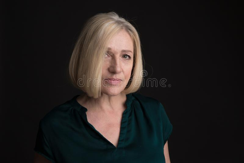 Portrait of blond adult woman isolated in a studio on a dark background. stock photo