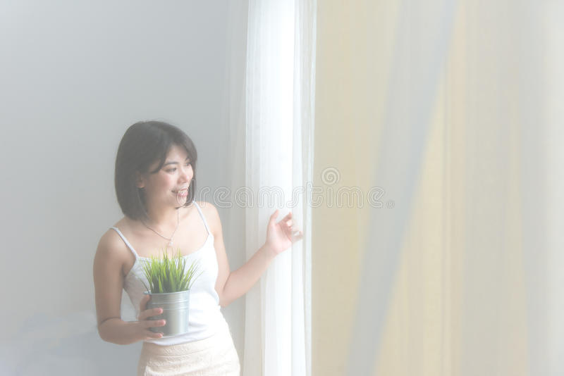 Portrait of blond and attractive woman standing next to the window behind the curtains in the morning, vintage tone, royalty free stock photo