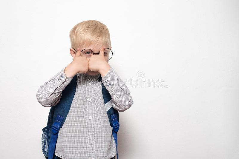 Portrait of a blond boy in glasses and with a school backpack on a white background shows a gesture class. School concept royalty free stock photos