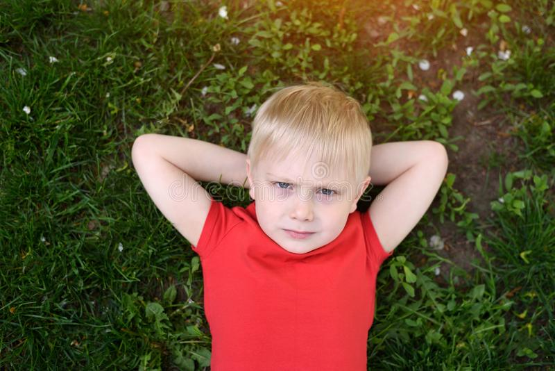 Portrait of a blond boy lying on the grass. Hands behind head. Rest at nature royalty free stock photo