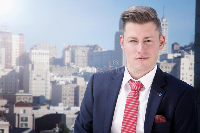 Portrait of blond businessman in front of city skyline stock image