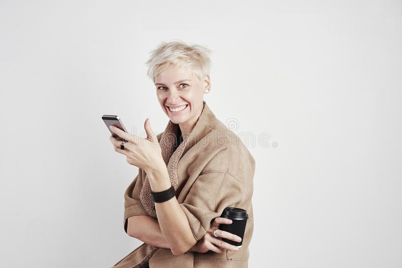 Portrait of blond caucasian woman smiling laughing emoticon drinks takeaway coffee, using smartphone on white background royalty free stock image