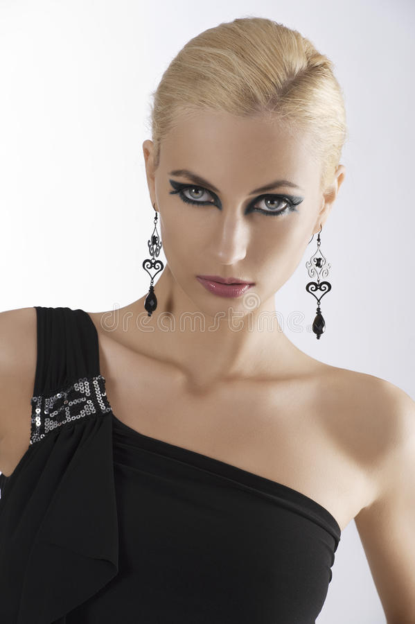 Portrait of blond girl in black dress. Portrait of blond attractive young woaman in black dress and black earring looking in camera with strong and eyes stock photography