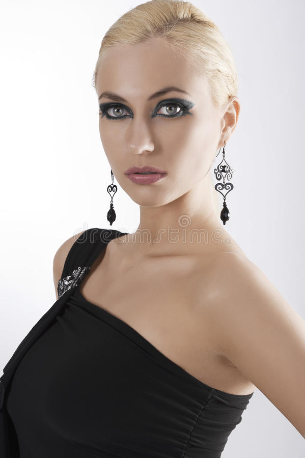 Portrait of blond girl in black dress posing. Portrait of blond attractive young woaman in black dress and black earring looking in camera with strong and eyes stock photography