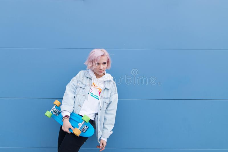 Portrait of a blond girl in a denim jacket standing on a blue background with a skate in her arms royalty free stock image