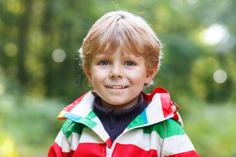 Portrait of blond little preschool boy in colorful waterproof r. Aincoat in autumn forest royalty free stock photos