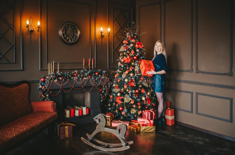 Portrait of blond woman with gift standing in dark living room near holiday Christmas tree royalty free stock photos