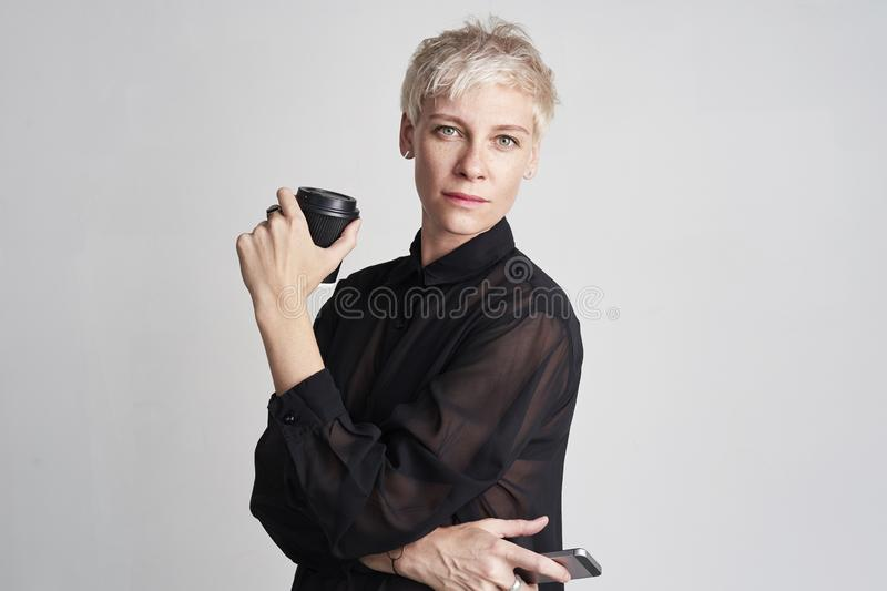 Portrait of blond woman with short hair wearing black shirt drinks takeaway coffee, using smartphone on white background. royalty free stock image