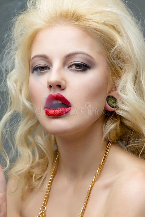 Portrait of blond woman smoking a cigarette. Portrait of young beautiful blond woman with red lips in the studio in a beautiful dress smoking a cigarette stock photos
