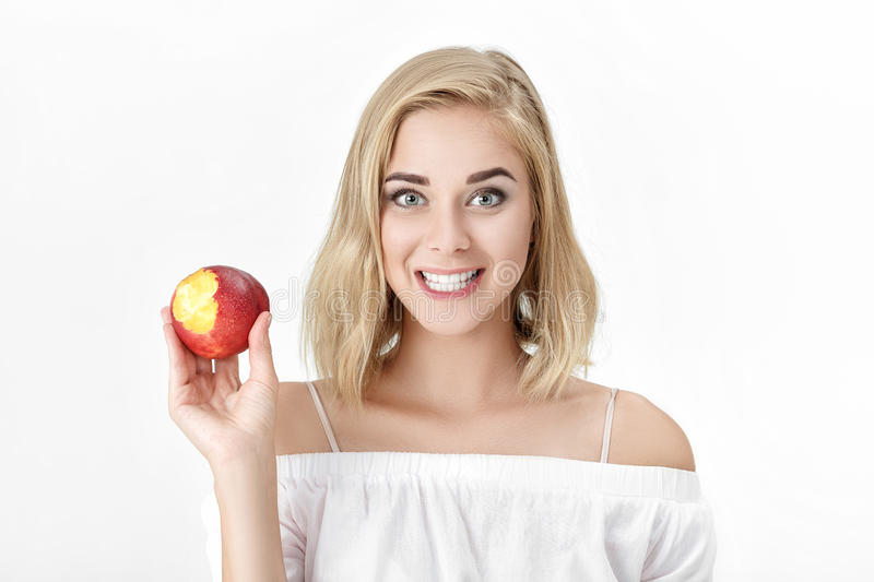 Portrait of blond woman with white teeth eating fresh nectarine. female smile stock photo