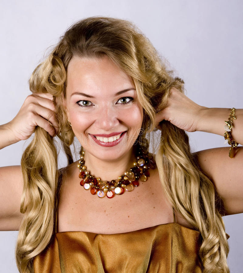 Portrait of blonde. Blonde looks straight into the camera and smiles broadly. She keeps her hair with both hands stock photos