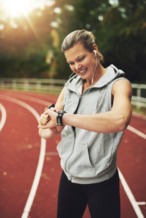 Portrait of blonde athlete looking at her watch royalty free stock image
