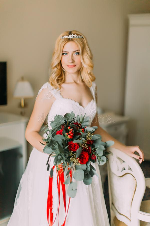 Portrait of blonde bride with wedding bouquet in bedroom royalty free stock photo