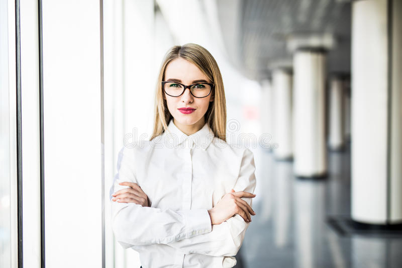 Portrait of blonde business woman with crossed hands in modern office. Office concept royalty free stock images