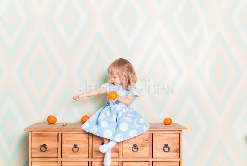 Portrait of blonde Caucasian baby girl with blue eyes in elegant dress and white socks sitting on wooden dresser with stock photography