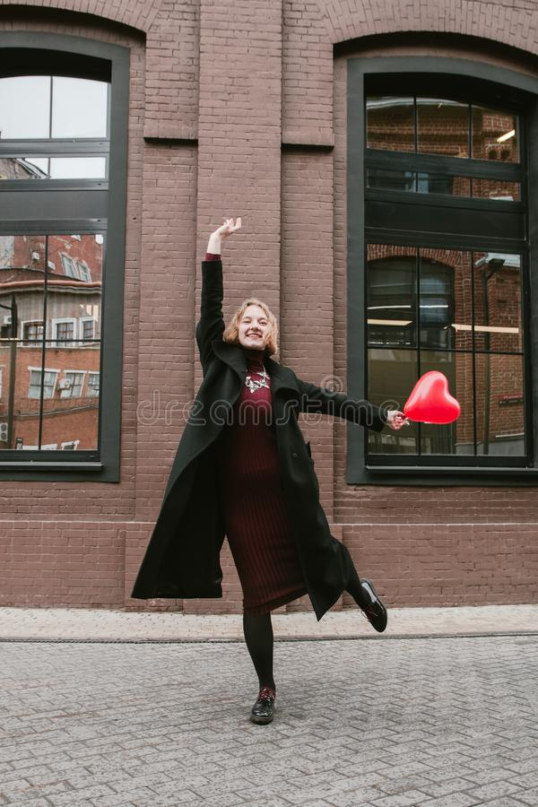 Portrait of Blonde curly girl posing with red heart shaped balloon royalty free stock images