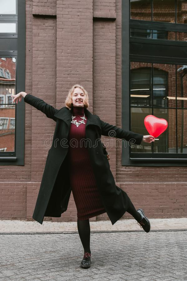 Portrait of Blonde curly girl posing with red heart shaped balloon stock photo