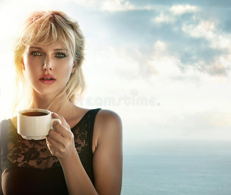Portrait of a blonde drinking coffee outdoors stock photo