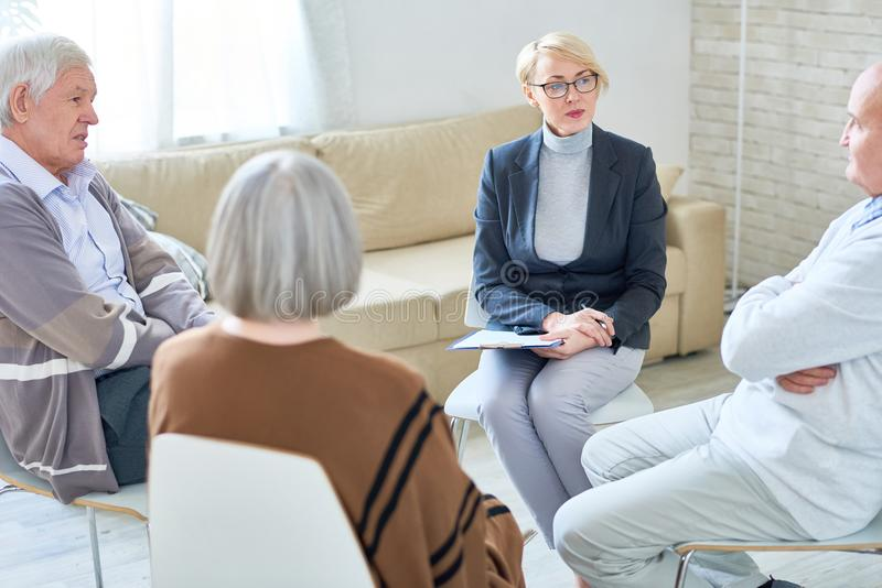 Therapy Circle in Retirement Home. Portrait of blonde female psychiatrist wearing glasses leading group therapy session for senior people sitting in circle in stock photography