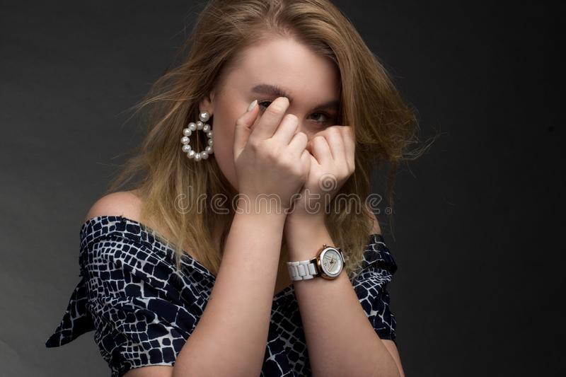 Portrait of blonde girl on a dark Studio background, he covers his face with his fists royalty free stock images