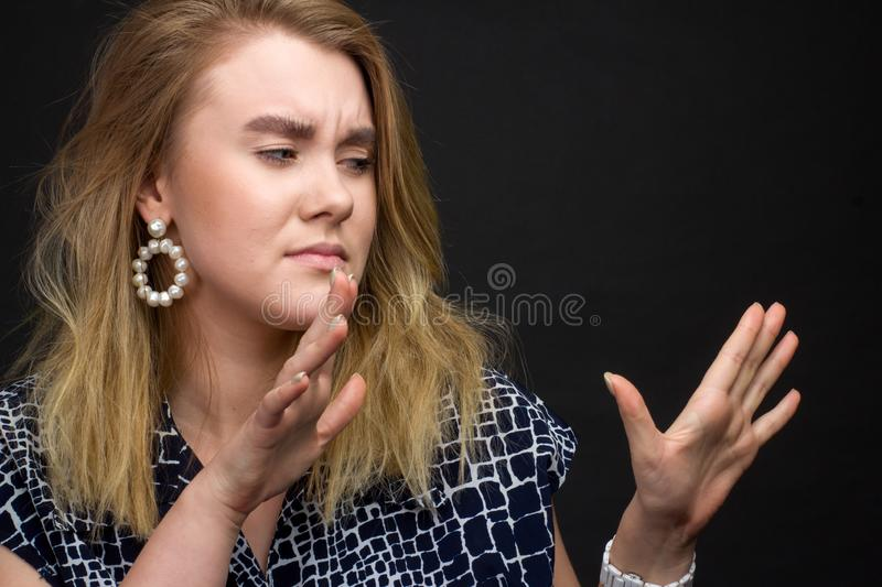 Portrait of blonde girl on a dark Studio background, hands and the face of expresses discontent, disgust royalty free stock image