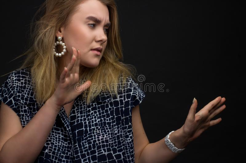 Portrait of blonde girl on a dark Studio background, hands and the face of expresses discontent, disgust stock images