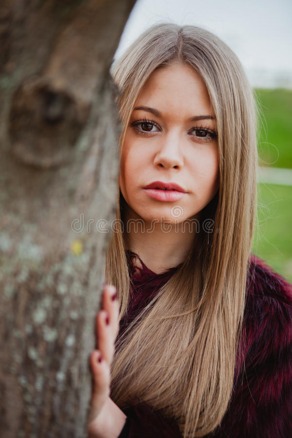 Portrait blonde girl next to a tree trunk. In a park stock photo