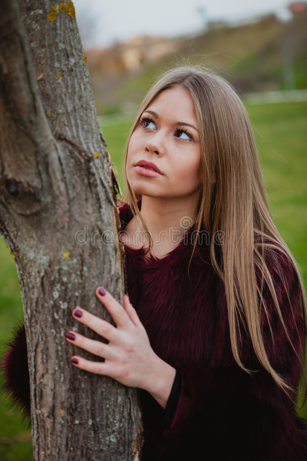 Portrait blonde girl next to a tree trunk. In a park royalty free stock images