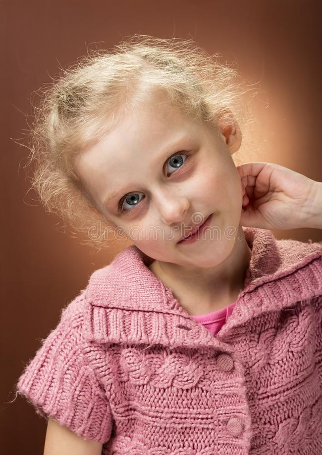 Portrait of blonde girl with pink shirt on brown background royalty free stock photo