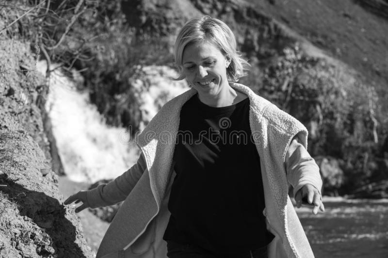 Portrait of a blonde Girl in a stylish jacket on the background of a waterfall. The concept of travel. black-white. Portrait of a blonde Girl in a stylish jacket stock photos