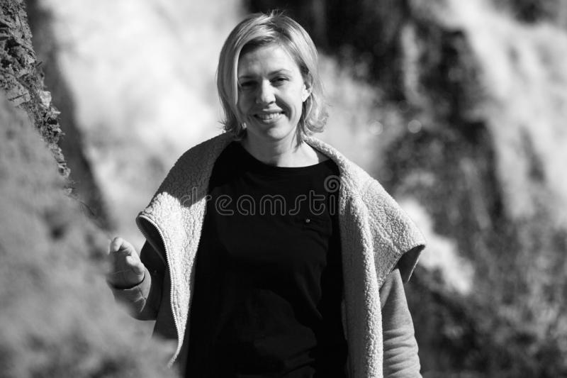 Portrait of a blonde Girl in a stylish jacket on the background of a waterfall. The concept of travel. black-white. Portrait of a blonde Girl in a stylish jacket royalty free stock images