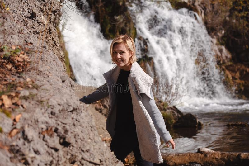 Portrait of a blonde Girl in a stylish jacket on the background of a waterfall. The concept of travel. Russia royalty free stock photography