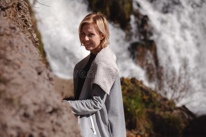 Portrait of a blonde Girl in a stylish jacket on the background of a waterfall. The concept of travel. Russia royalty free stock images