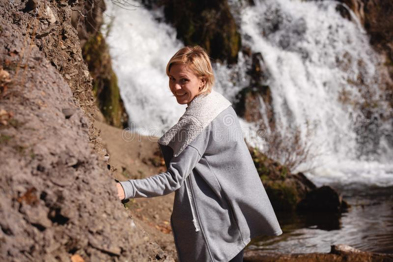 Portrait of a blonde Girl in a stylish jacket on the background of a waterfall. The concept of travel. Russia stock photos