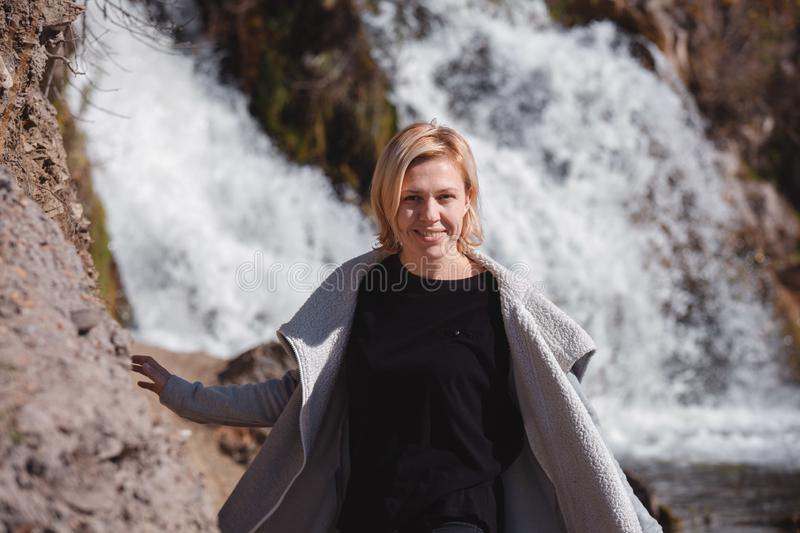 Portrait of a blonde Girl in a stylish jacket on the background of a waterfall. The concept of travel. Russia stock photography