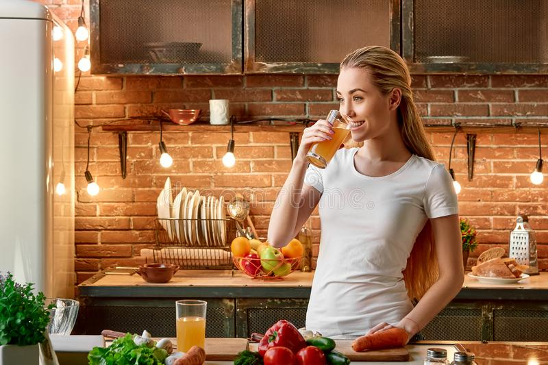 Keep calm eat fruits plus vegetables. Happy young woman cooking vegetables in modern kitchen. Cozy interior stock images